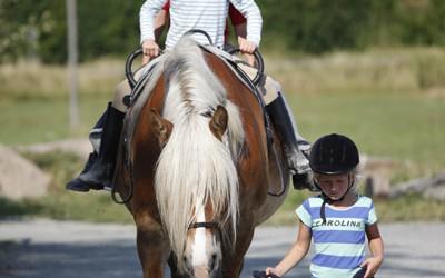 Ovanligt läger juli -13. Carro leder Saga<br> med Ingrid & Adrian på ryggen.