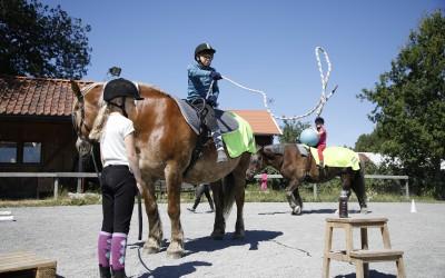 Maja leder Saga och Edvin kastar lasso från hästryggen. Ovanligt hästdagläger juli 2018.